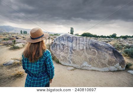 Woman Tourist Near Ancient Stone Painting