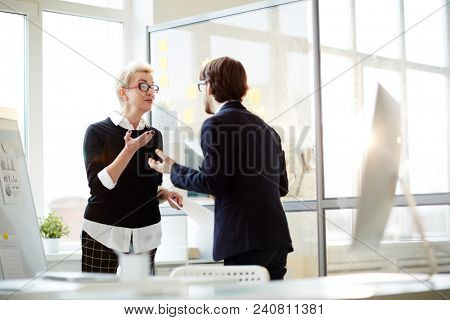 Group of emotional managers discussing their joint project while standing at modern open plan office, they gesticulating vigorously, lens flare