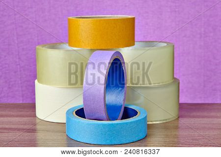 Several Rolls Of Duct Tape In Different Colors And For Different Purposes Are On The Table On A Purp