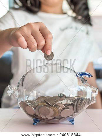 Money Saving Banking Concept With Girl Kid Holding Coin Inserting In Glass Piggy Bank For Educationa