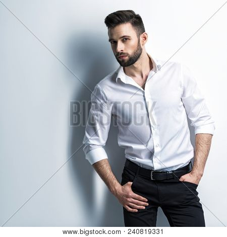 Handsome man in white shirt and black trousers - posing  at studio. Attractive guy with fashion hairstyle.  Confident man with short beard. Adult stylish boy with brown hair.