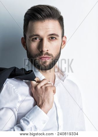 Handsome man in white shirt holds the black suit - posing  over wall. Attractive guy with fashion hairstyle.  Confident man with short beard. Adult boy with brown hair.