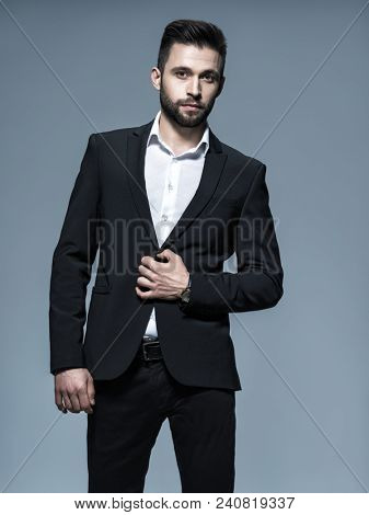 Handsome man in black suit with white shirt  - posing  at studio. Attractive guy with fashion hairstyle.  Confident man with short beard. Adult boy with brown hair. Full portrait.