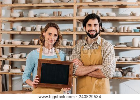 Couple Of Owners Holding Chalkboard In Wooden Frame In Pottery Workshop With Ceramics On Shelves