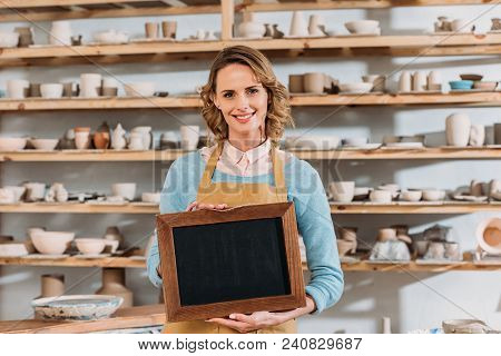 Beautiful Smiling Owner With Chalkboard In Pottery Workshop