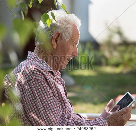 Old Man Sitting On Bench In Park And Looking At Tablet