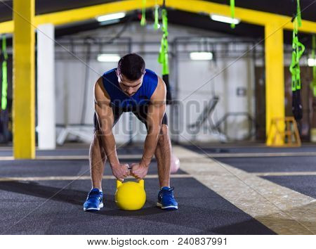 young  man athlete exercise with fitness kettlebell at fitness gym