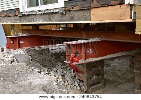 An Old House Rests On  65 Foot Long Steel Girders As A New Concrete Basement And Foundation Is Being