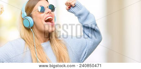Young woman listen to music with headphone happy and excited celebrating victory expressing big success, power, energy and positive emotions. Celebrates new job joyful