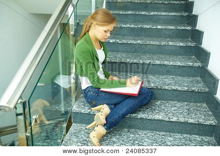 Photo of pretty girl sitting on stairs of college and writing something