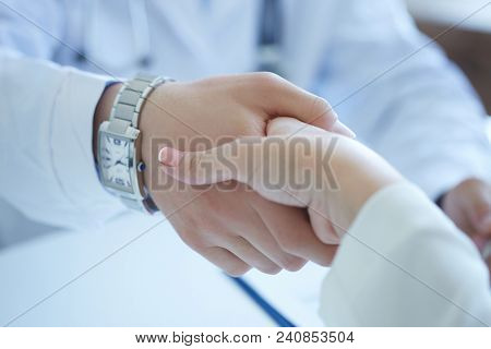 Male Doctor Shaking Hands With Patient. Partnership, Trust And Medical Ethics Concept. Thankful Hand
