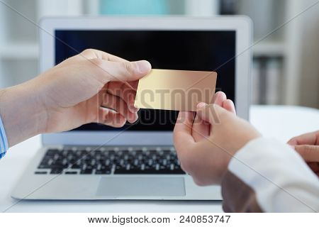 Closeup Shot Of A Woman's Hand Giving A Payment Credit Card To The Seller In Computer Store. . Shall