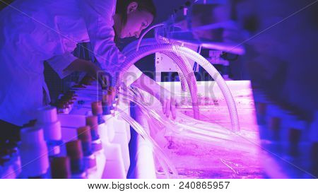 A Woman Scientist In A Lab Coat Conducting An Experiment In A Lab With Purple Lightning And A Large