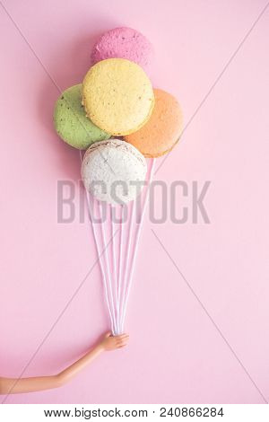 Doll Hand Holding Colorful Macaroons In Form Of Helium Balloons Minimal Creative Concept.