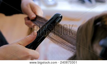 Professional Hairdresser, Stylist Doing Hairstyle And Using Straightener On Beautiful Long Hair Of C
