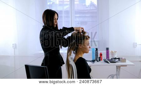 Professional Hairdresser, Stylist Doing Hairstyle For Young Pretty Woman With Long Hair And Using Ba