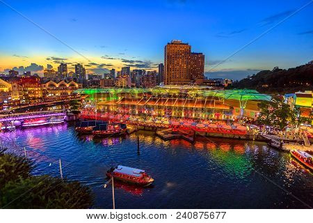 Scenic aerial view of Clarke Quay and Riverside area at blue hour in Singapore, Southeast Asia. Waterfront skyline reflected on Singapore River. Popular attraction for nightlife. poster