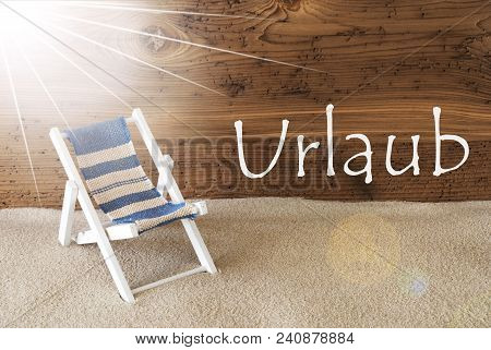 Sunny Summer Greeting Card With Sand And Aged Wooden Background. German Text Urlaub Means Holiday. D