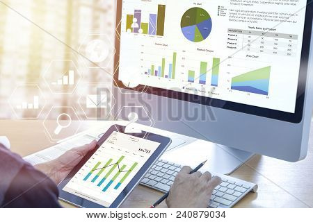 Businessman In Front Of Modern Computer With Colorful Pie And Bar Graphs Analysing Business Performa