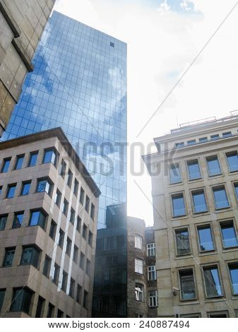 A Modern Skyscraper Made Of Glass And Steel Stands Among The Classic Buildings In The Center Of The