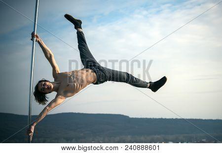 Athletic Guy Make Acrobatic Elements On Pylon. Strong Man Dancer Workout On Pole. Pole Dance Sport.