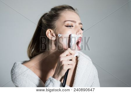Woman with face covered with foam holds straight razor in hand. Girl on busy face wears bathrobe, grey background. Barber and shaving concept. Lady shaves her face with sharp blade of straight razor. poster