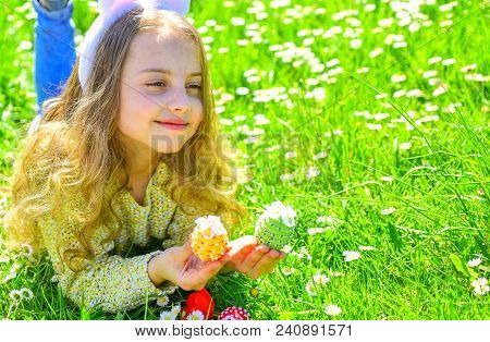 Child With Cute Bunny Ears Lying At Meadow. Cute Child Lay On Grass With Egg In Hands. Little Girl H