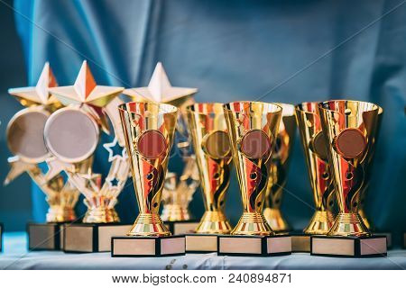 Different Champion Golden Trophy, Trophies. Winners Cups On Blue Cloth Background