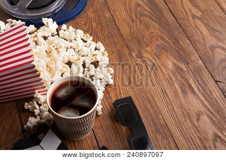 Cinema Background. Clapperboard, Popcorn, Soda Glasses And Film Reel On Wooden Table, Copy Space. Mo