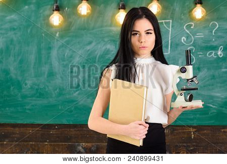 Teacher Of Biology Holds Book And Microscope. Lady In Formal Wear On Calm Face In Classroom. Biology