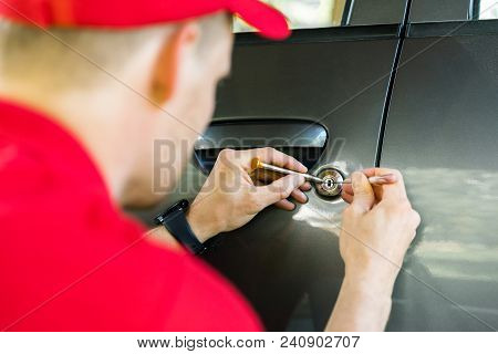Locksmith In Red Uniform Opening Car Door With Lockpicker