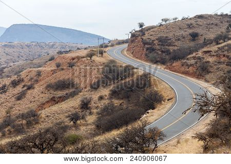 A Winding Mountain Road Running Through The Arid Terrain Of The Middle East. Stock Photo