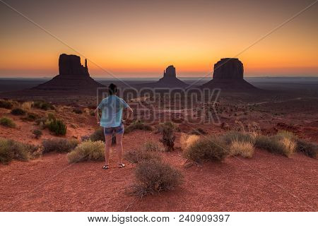 Girl Admiring The Sunrise. View On Merrick, East And West Mitten Butte At Sunrise. Navajo Tribal Par