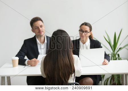 Back Close Up View Of Female Applicant Being Interviewed By Two Hr Managers Reading Her Resume, Chec