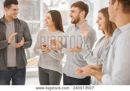 Young people applauding during group therapy, indoors