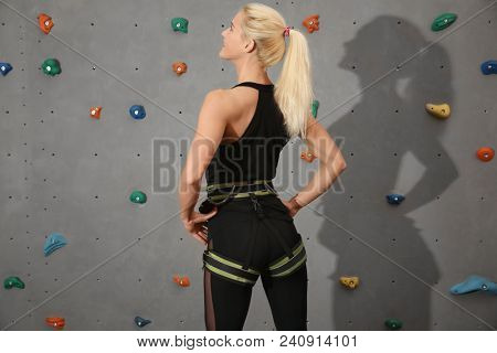 Young sporty woman in climbing gym
