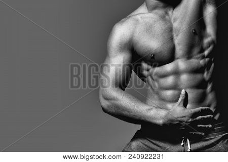 Mens Heals Body Care. Man With Muscular Sexy Body And Six Packs On Torso In Pants In Studio On Grey