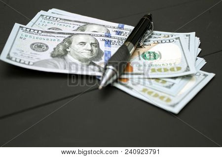 Dollars money cash on black background. Heap of money and pen. Writer fee