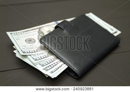 Dollars money cash on black background. Heap of money and wallet