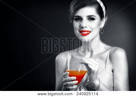 Pin up retro girl drink bloody Mary cocktail. Black and white photos with red color accents. Pin-up retro female style. Girl vintage style wearing dress. Black and white retro portrait with red accent