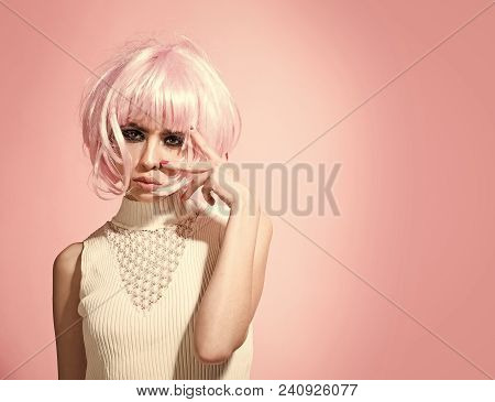 Fake, False Concept. Woman In Pink Wig Hair On Rosy Background. Girl With Smokey Eyes, Makeup Face.