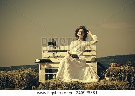 Woman Reading Book On Grey Sky, Vintage Filter. Lady In White Dress And Wreath On Sunny Day. Summer