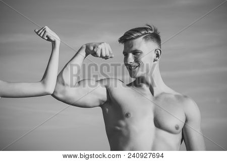 Man With Strong Hand Biceps, Triceps Smile At Female Hand On Blue Sky. Contrast, Competition, Confli