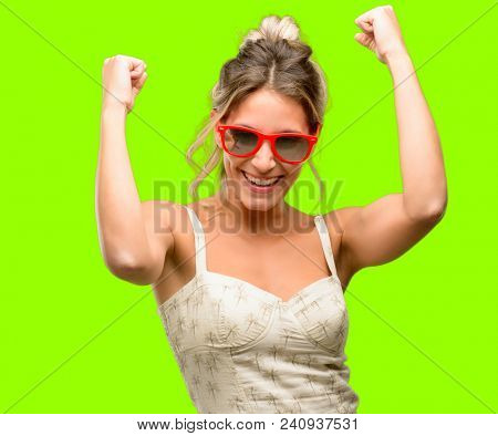 Young beautiful woman wearing red sunglasses happy and excited celebrating victory expressing big success, power, energy and positive emotions. Celebrates new job joyful