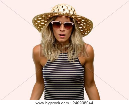 Young woman using sunglasses wearing summer hat scared in shock, expressing panic and fear
