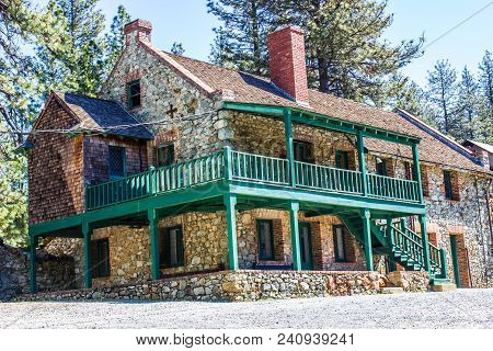 Vintage Two Story Building With Stone Walls & Balcony