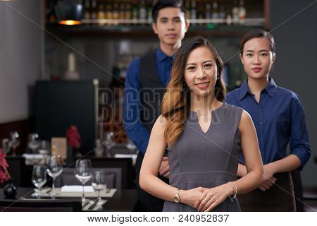 Portrait Of Cheerful Female Restaurant Owner Standing In Front Of His Employees