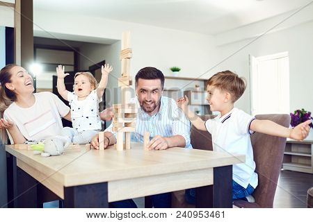 A Cheerful Family Plays Board Games Sitting At A Table Indoors.