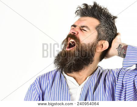 Hipster with beard and mustache with messy hair wears bathrobe, close up. Man with yawning sleepy face on white background. Morning yawning concept. Guy awake with mouth opened in yawn, copy space. poster