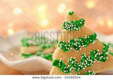 Freshly baked christmas tree cookies with defocused golden lights in background.  Macro with extremely shallow dof and copy space.